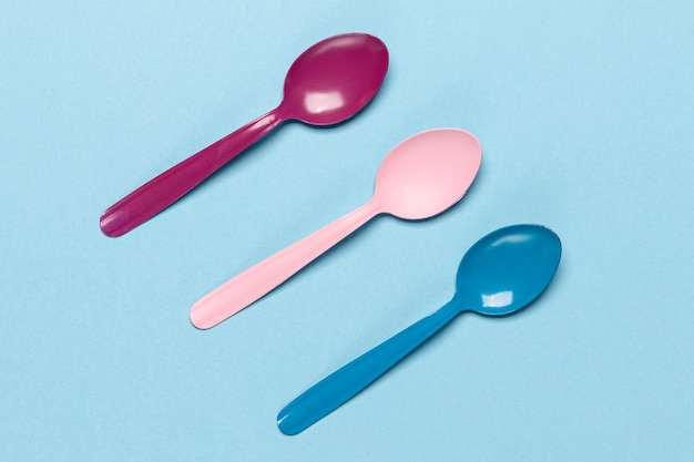 Variety of coloured spoons on blue background