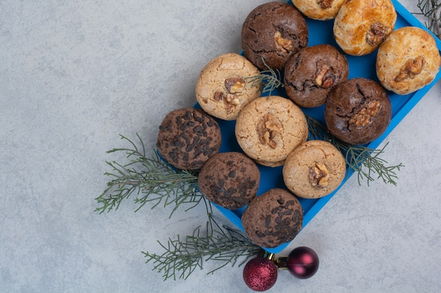 Variety of cookies on blue plate with christmas balls