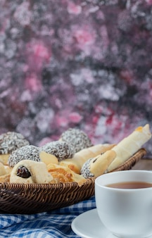 Varietà di biscotti nel vassoio con una tazza di tè da parte.