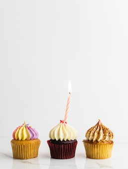 Variety cupcakes with candle birthday party on white background, anniversary concept