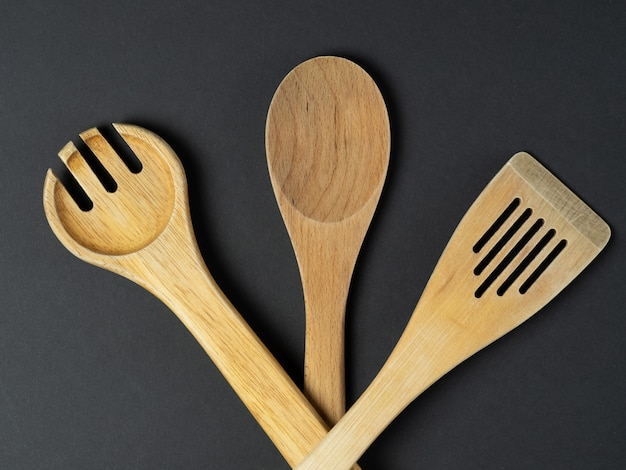 A variety of cutlery and natural wood laid out on a black background. concept of renewable sources and objects made of wood
