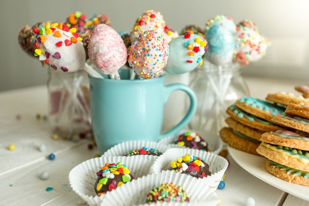 Variety of decorated candies, cake pops and cookies on white wooden desk