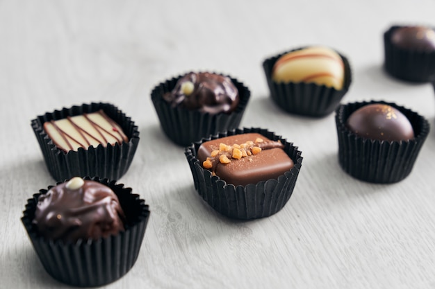 Variety of delicious chocolate candies on wooden background