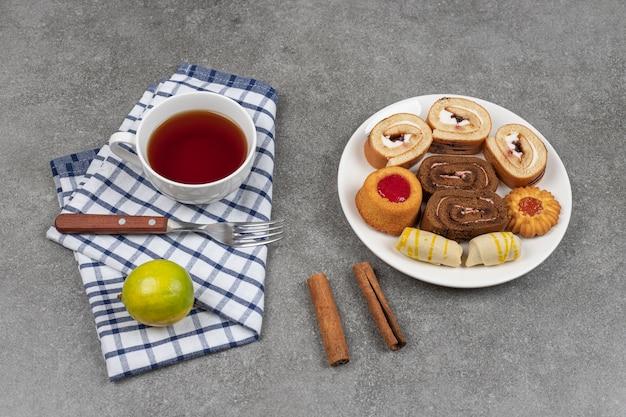 Varietà di deliziosi biscotti sul piatto bianco con una tazza di tè