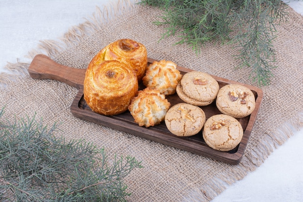 Variety of delicious cookies on wooden board.