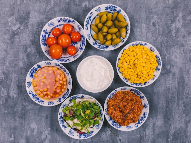 Variety of delicious mexican dishes arranged over concrete background