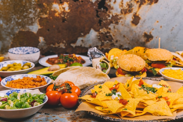 Variety of delicious mexican dishes over rusty metal background