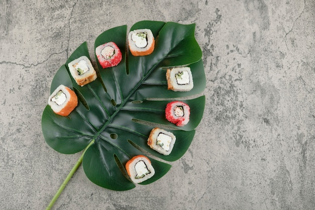 Variety of delicious sushi rolls and green leaf on stone surface.