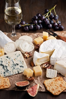 Variety of different cheese with wine, fruits and nuts. camembert, goat cheese, roquefort, gorgonzolla, gauda, parmesan, emental