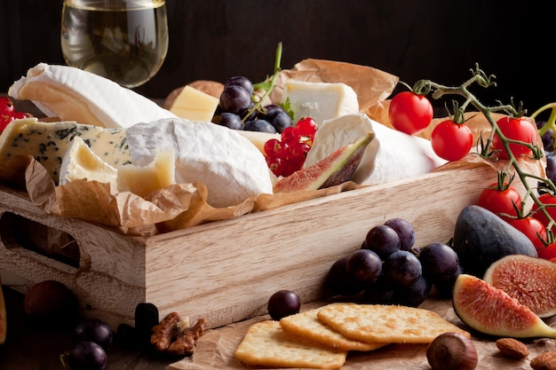 Variety of different cheese with wine, fruits and nuts.