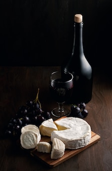 Variety of different cheese with wine, fruits.