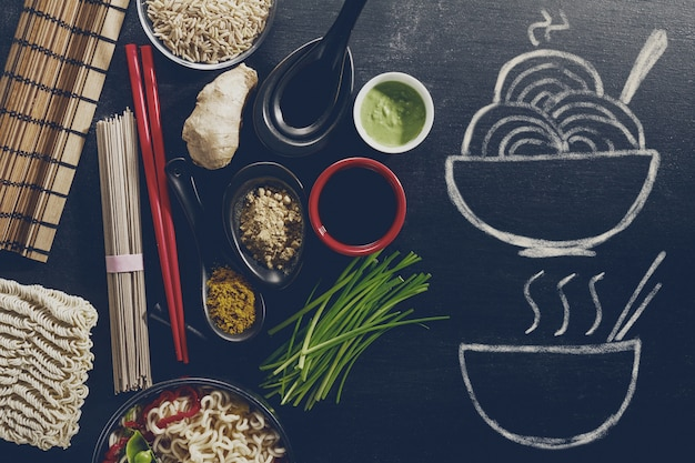 Variety different many ingredients for cooking tasty oriental asian food with hand drawn ready dish on chalkboard. top view with copy space. dark background. above.