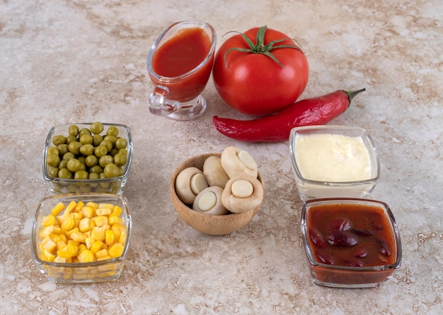 Variety of dressings and toppings, arranged and displayed on marble surface.