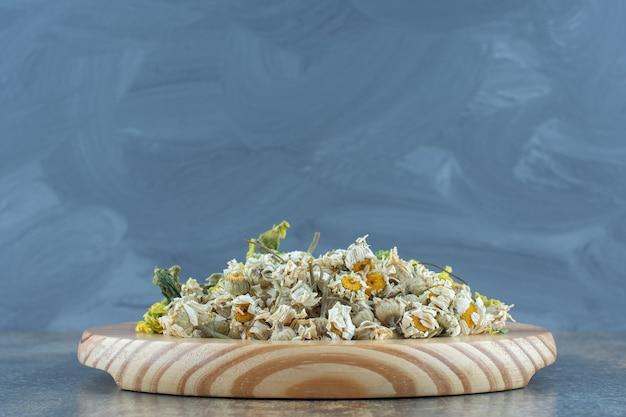 Varietà di fiori secchi sul piatto di legno.