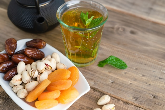 Variety of dried fruits with glass of mint tea on wooden background. copy space. top view.