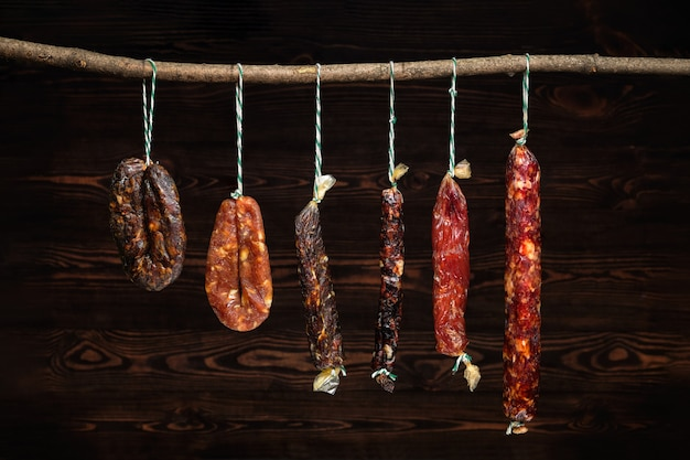 Variety of dried sausage on twine hanging in country wooden barn