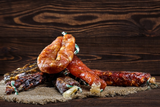 Variety of dried sausage on wooden table