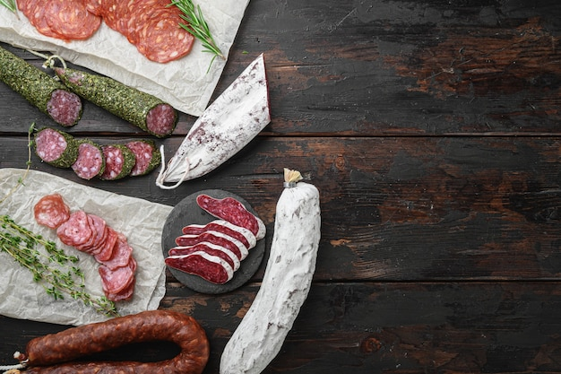 Variety of dry cured  chorizo, fuet and other sausages cut in slices with herbs on old wooden table, flat lay with copy space.