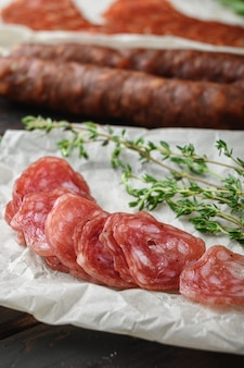 Variety of dry cured chorizo, fuet and other sausages cut in slices with herbs on old wooden table