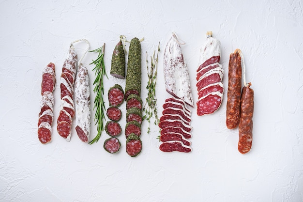 Variety of dry cured fuet and chorizosalami sausages, whole and sliced on white surface, top view.