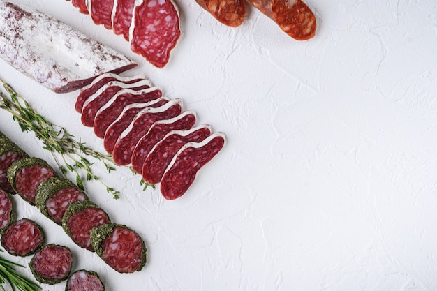 Variety of dry cured fuet and chorizosalami sausages, whole and sliced on white textured surface, topview with space for text.