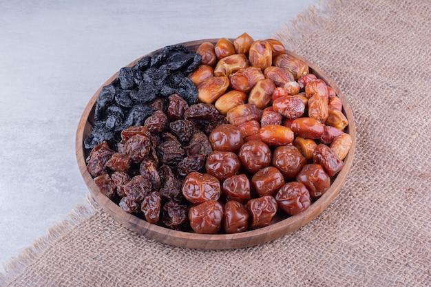 Varietà di frutta secca su un piatto di legno