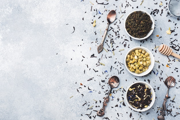 Variety of dry tea leaves and flowers in bowl on grey background.