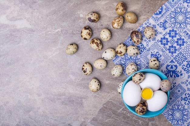 Varietà di uova in una tazza blu e sul terreno.