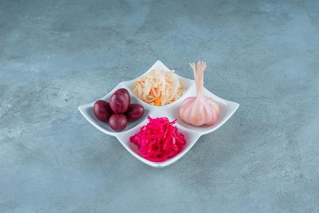 Una varietà di verdure fermentate in un piatto, sul tavolo di marmo.