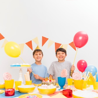 Variety of food on table with two boys holding balloons in party