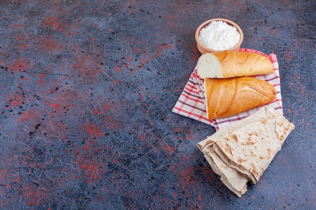 Variety of fresh fragrant bread with bowl of flour on blue surface.