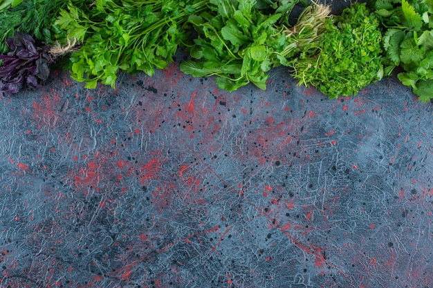 A variety of fresh greens, on the marble background.