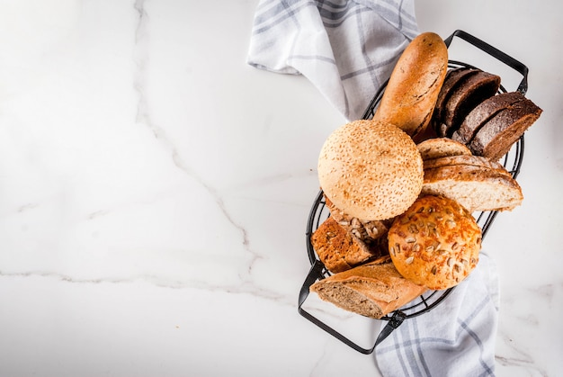 Variety of fresh homemade grain bread, in a metal basket, white marble  copyspace top view