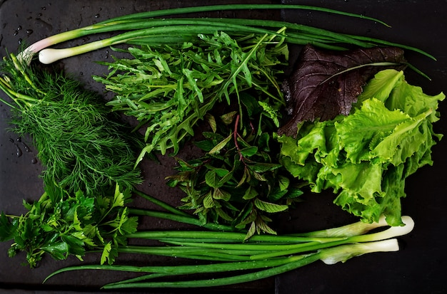 Variety fresh organic herbs (lettuce, arugula, dill, mint, red lettuce and onion) in rustic style. top view
