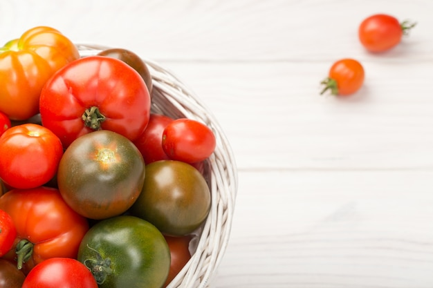 Variety fresh tomatoes in basket on wooden