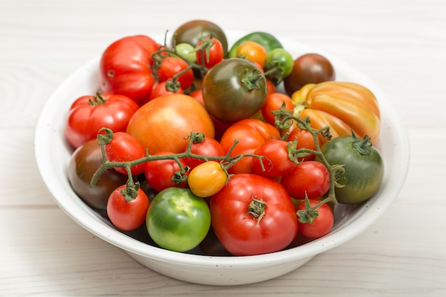 Variety fresh tomatoes in bowl on wooden