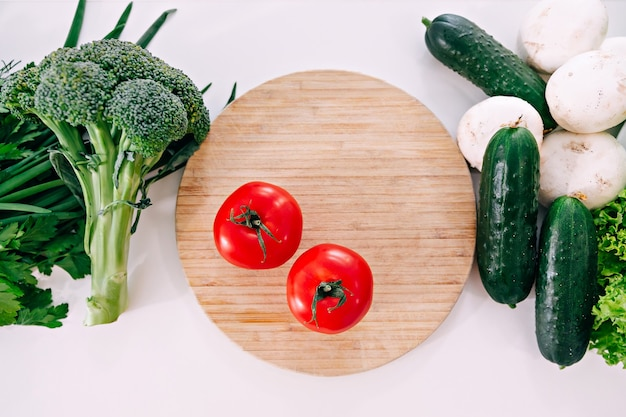Variety of fresh vegetables placed on wooden chopping board with knife on table.