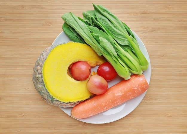 Variety of fresh vegetables on white plate against wooden board background.