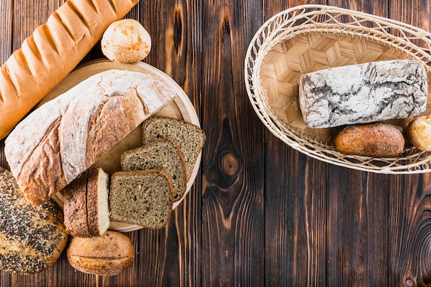 Variety of freshly baked breads on plate and basket over the wooden backdrop
