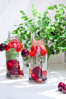 Variety of fruit with detox water in glass small bottles. refreshing summer drinks. healthy diet concept.