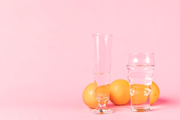 Variety of glasses filled with water and oranges