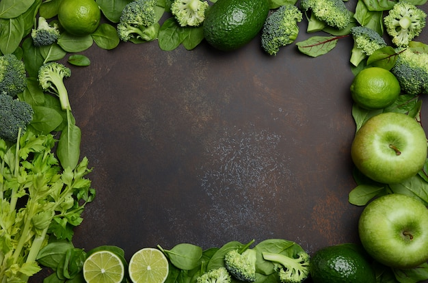 Variety of green fruits and vegetables on a dark concrete