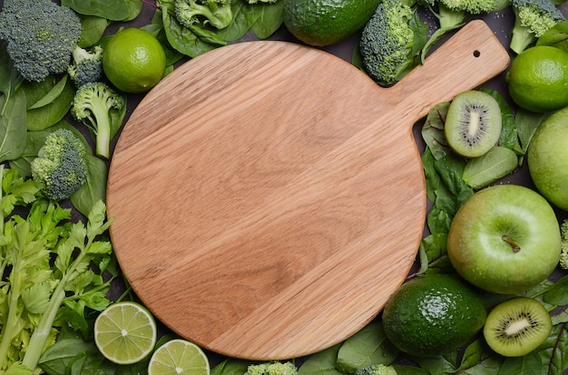 Variety of green fruits and vegetables with empty wooden cutting board