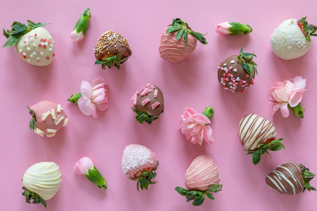 Variety of handmade chocolate covered strawberries with different toppings and flowers on pink background