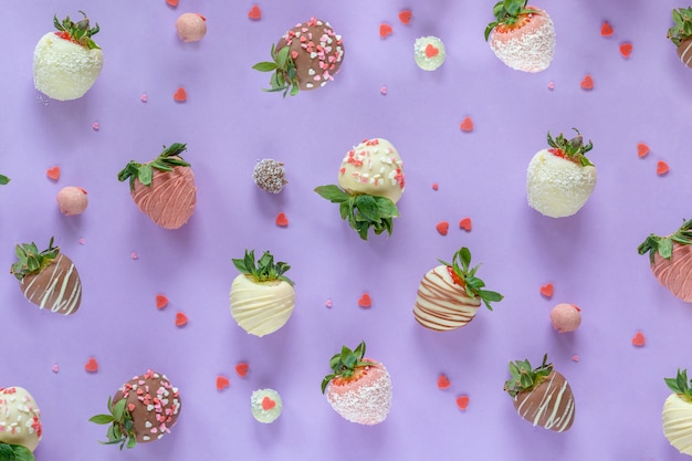 Variety of handmade chocolate covered strawberries with different toppings on purple background