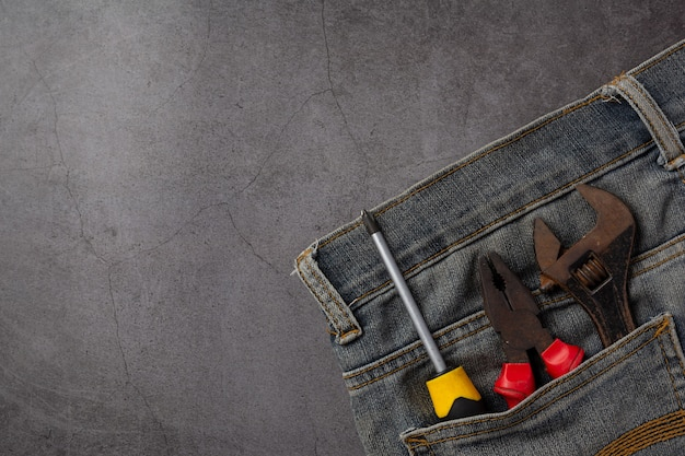 Variety handy tools and jeans on dark background