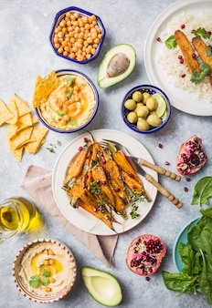 Variety of healthy vegan snacks, gourmet dips. hummus,  roasted carrots, rice with tempeh in ceramic bowls viewed from above, plant based food