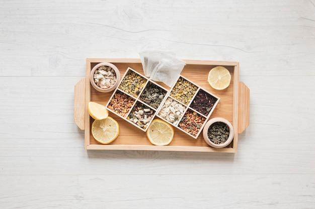 Variety of herbs and dried chinese chrysanthemum flowers arranged in small container on wooden tray