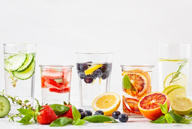 Variety of herbs and fruits flavored infused water and their ingredients. summer refreshing drink. health care, fitness, healthy nutrition diet concept.