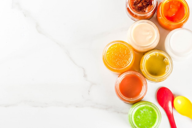 Variety of homemade baby vegetable and fruit puree,  white marble  copyspace top view